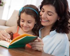 Mujer y niña leyendo juntas sonriendo